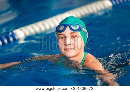 Cute Little Girl Training In A Swimming Pool