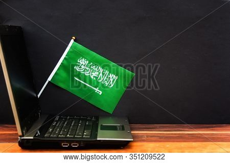 Flag Of Saudi Arabia , Computer, Laptop On Table And Dark Background