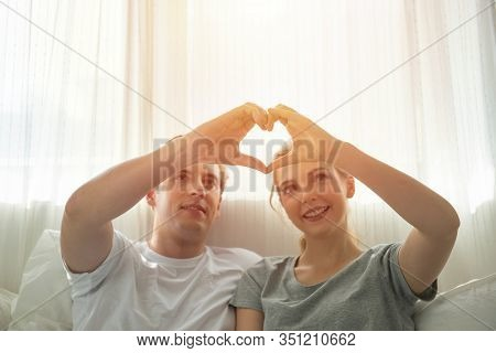 Love Is All Around, Beautiful Young Caucasian Couple Sitting Close To Each Other On Bed And Looking