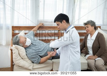 Asian Senior Elderly Old Man With Mask On Lying On Sofa While Young Caucasian  Doctor Sit On Knee Ch