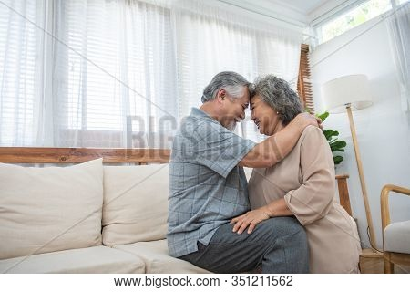 Laughing Retirees Pretty Asian Couple Sitting On Couch At Home, Spouses Having Candid Healthy Toothy