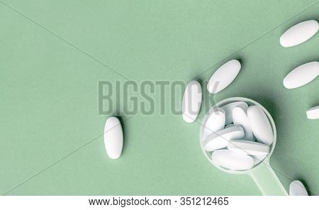White Pills In Dosage Spoon For Drugs On A Aqua Menthe Background, Close-up