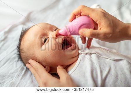 Mother Using Baby Nasal Aspirator Mucus Nose Suction