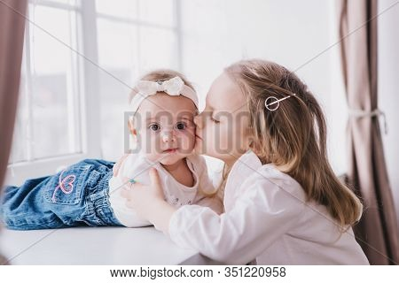 Two Cute Sisters Sitting Near Window Close To Each Other And Playing At Home.little Sister Hugging H