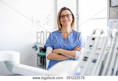 A Portrait Of Dental Assistant In Modern Dental Surgery, Looking At Camera.