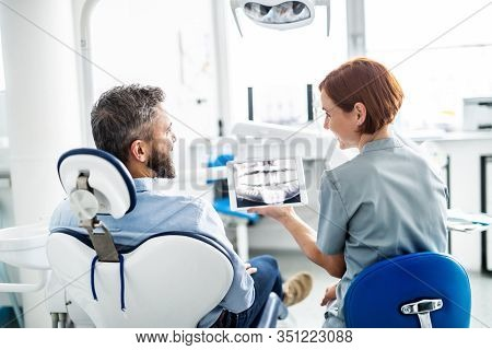 Rear View Of Man And Dentist In Dental Surgery, Annual Check-up.