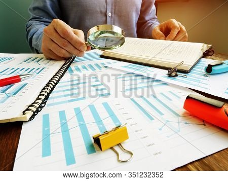 Auditor Makes Financial Company Audit And Uses Magnifying Glass For Checking Report.