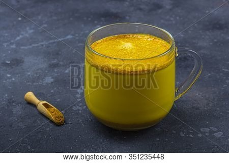 Traditional Indian Drink Turmeric Milk Is Golden Milk In Glass Mug With Turmeric On Dark Background.
