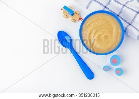 Baby Food. Fresh Homemade Applesauce. Blue Bowl With Fruit Puree On Fabric And Kids Toys On Table. T