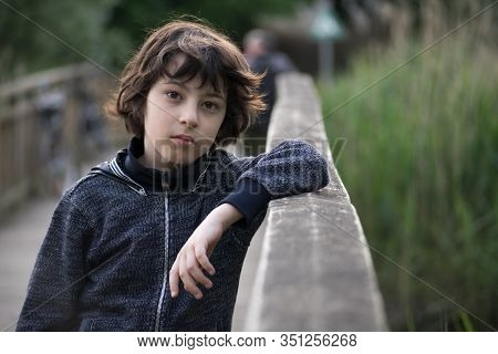 Portrait Of A Sad Boy Near A Wooden Fence.