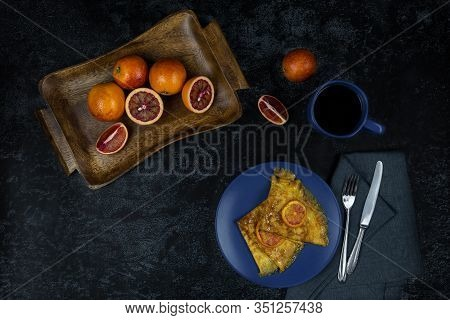 Two Crepe Suzette On A Plate, Golden Toasted With Slices Of Red Orange And In Syrup On A Dark Backgr