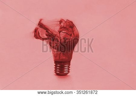 One Broken Light Bulb On A Blue Background With Smoke. Overdue Idea Concept.