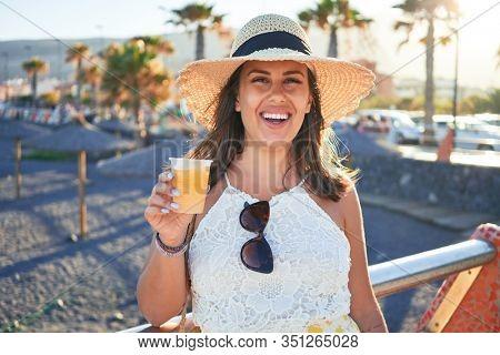 Young beautiful woman smiling happy enjoying summer vacation drinking fresh slush