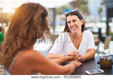 Beautiful mother and daugther sitting at terrace of a restaurant speaking and smiling
