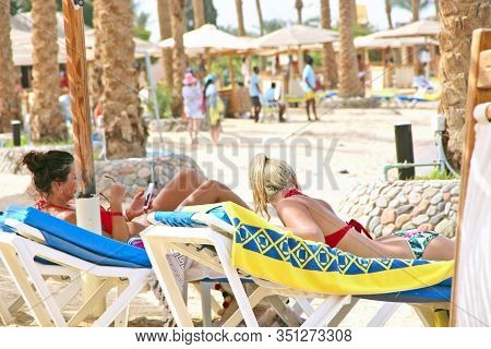 Young Women Laying On Chaise-longue In Shadow Under Beach Umbrella Enjoying Tropic Vacation. Women R