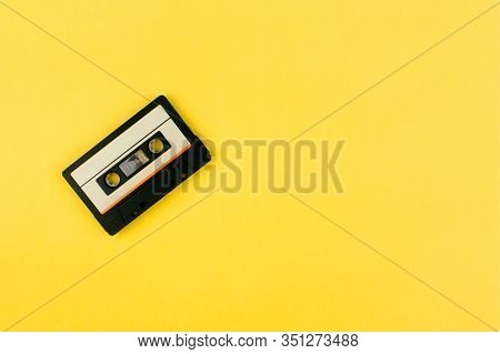 Audio Cassette Tape Flat Lay On Colorful Yellow Background Top View With Copy Space. Creative Fashio
