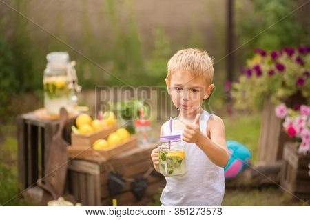 Funny Boy With Homemade Lemonade Close-up. A Boy In The Backyard Sells Homemade Lemonade And Copy Sp