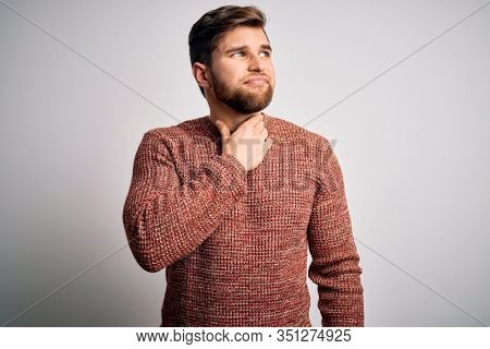 Young blond man with beard and blue eyes wearing casual sweater over white background Touching painful neck, sore throat for flu, clod and infection