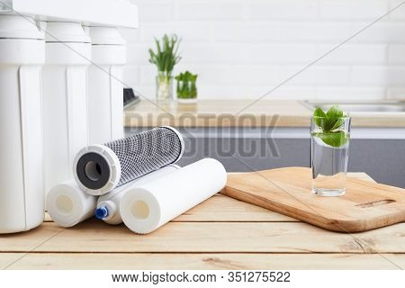 A Glass Of Clean Water With Osmosis Filter And Cartridges On Wooden Table In A Kitchen. Concept Filt