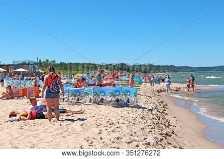 People Relax On Beach Of Baltic Sea During Summer Vacation. Baltic Sea Coast With Vacationers. Famil