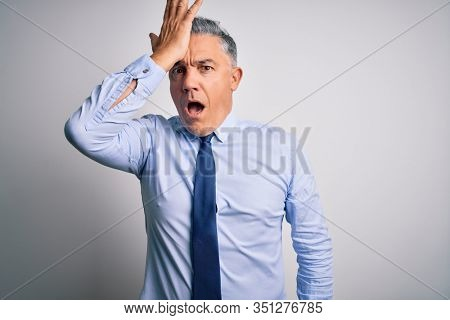 Middle age handsome grey-haired business man wearing elegant shirt and tie surprised with hand on head for mistake, remember error. Forgot, bad memory concept.
