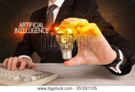 Businessman holding lightbulb with ARTIFICIAL INTELLIGENCE inscription, Business technology concept