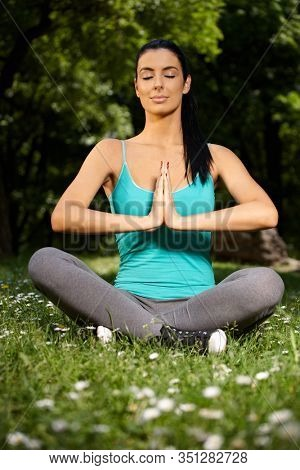 Young attractive female practicing yoga in nature, eyes closed, prayer position.