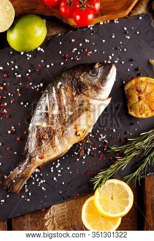 Delicious Roasted Dorado Or Gilt-head Bream Fish With Lemon And Orange Slices, Spices, And Fresh Ros