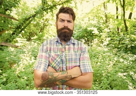 Summer Style. Bearded Man Keeping Arms Crossed In Casual Style On Natural Landscape. Brutal Hipster