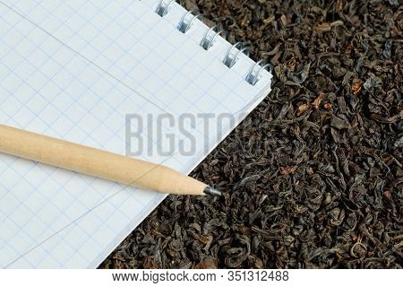 Notebook With Pencil On Dry Black Tea. Product Volume Inventory Concept. Close Up.