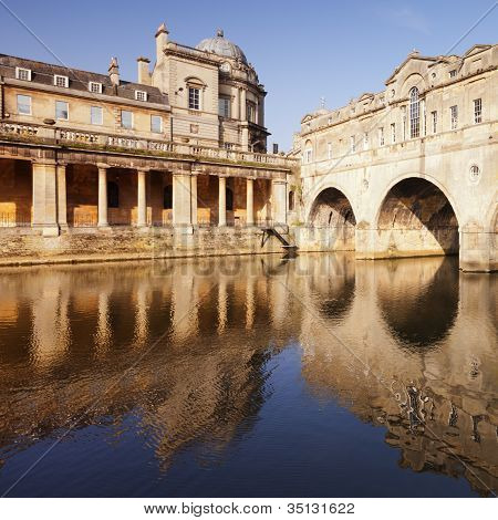 Pulteney Bridge and Colonnade Bath England on a bright spring morning reflected in the River Avon. The bridge was designed by Robert Adam and completed in 1773. It is one of only four bridges oin the world with shops across the full span on both sides and poster