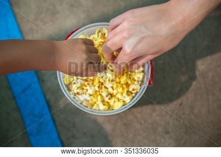 Close up photo of two hands reaching for buttered popcorn in a bucket at an amusement park