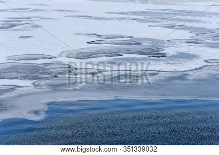 Winter Landscape. Landscape At The Border Of Blue Water And Frozen, Snowy And Icy Space. Ice Hummock