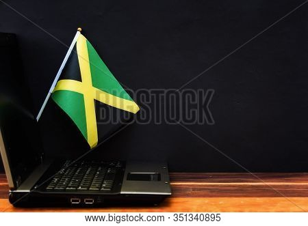 Flag Of Jamaica , Computer, Laptop On Table And Dark Background