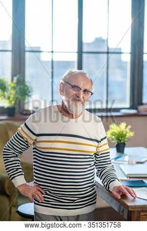 Grey-haired Bearded Man In Eyewear Smiling Nicely Standing Near The Table