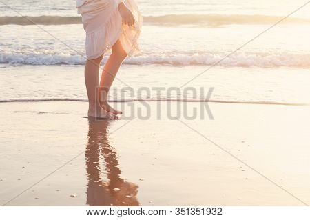 Beautiful Woman Legs On The Beach With Sea Surf At Sunset. Romanc Step On Surf