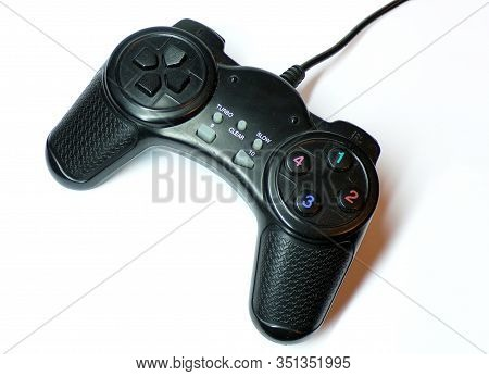 The Game Joystick Is Isolated On A White Background. Gamepad With Wire For Video Games On Game Conso