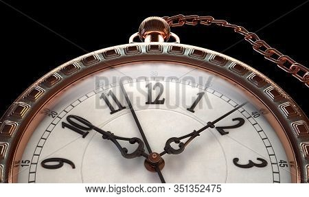 A Closeup Of An Intricate Copper Antique Pocket Watch Attached To A Chain On An Isolated Dark Backgr