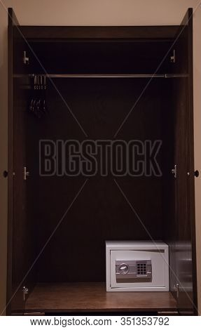 Digital Key Safe Storage Deposit Box In Wooden Clothes Hanging Wardrobe Background. Hotel Furniture,