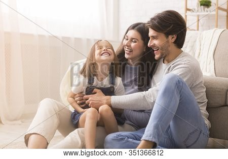 Family Love. Playful Parents Tickling Their Little Daughter, Having Fun Together At Home In Living R