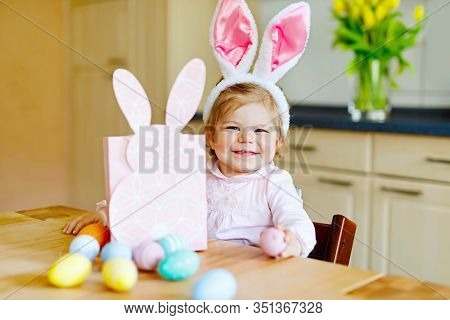 Cute Little Toddler Girl Wearing Easter Bunny Ears Playing With Colored Pastel Eggs. Happy Baby Chil