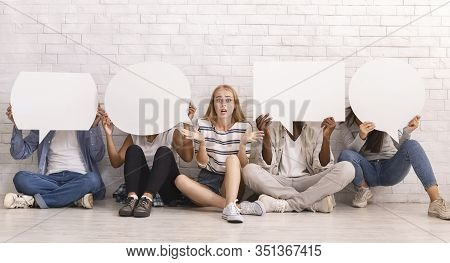 No Private Opinion. Lost Girl Sitting Among Multiracial Friends Covering Faces With Speech Bubbles,