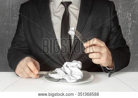 A Man Without A Face In A Black Suit And Tie Sits At A Table And Prepares To Eat A Piece Of A Sheet