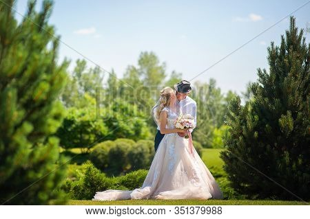 The Bride And Groom On A Walk In The Summer. Newlyweds In The Park. Summer Wedding In Nature, Ukrain