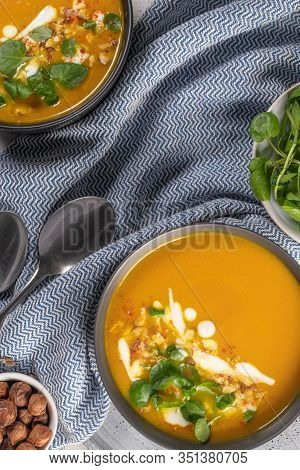 Pumpkin Soup With Watercress On Table. Seasonal Autumn Food - Spicy Pumpkin Soup In Bowl.