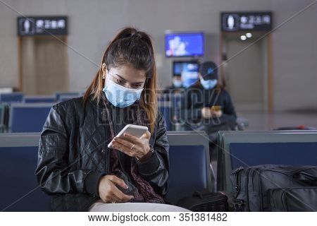 The Girl Is Sitting At The Airport Leaving China. Holding A Phone. Medical Mask On Her Face. Coronav