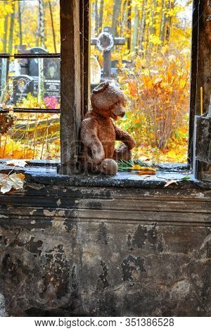 Weathered Teddy Bear Toy With Yellow Maple Leaf And Flowers In Opening Of Old Crypt With Child Buria