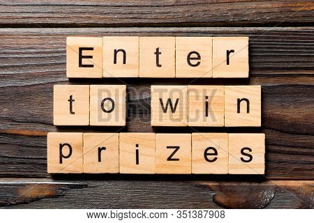 Enter To Win Prizes Word Written On Wood Block. Enter To Win Prizes Text On Wooden Table For Your De
