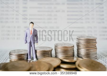 Miniature Of Standing Business Man With Row Of Coins And Blurred Bankbook