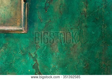 Wall With Relief Decorative Art Plaster Painted In Malachite Green Paint With Golden Yellow Streaks.
